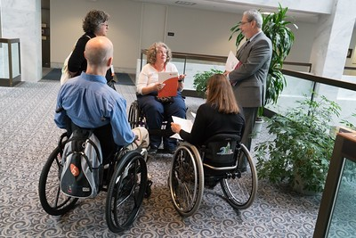 People in wheelchairs and two people standing having a discussion