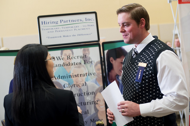 Man talking to woman among booths at a career fair