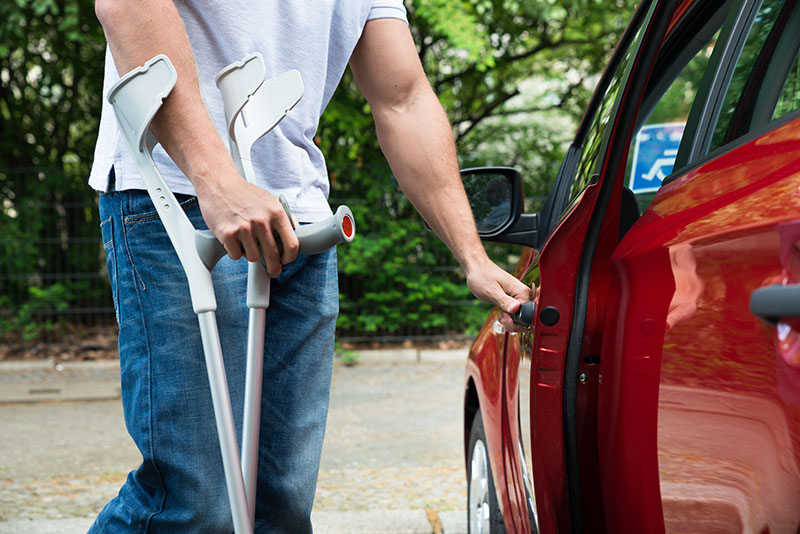 Man with crutches opening car door
