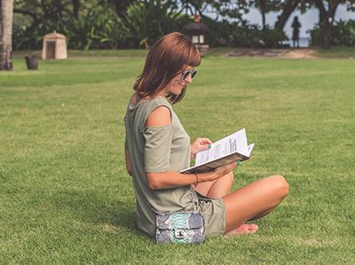 Image of a woman sitting on grass and reading