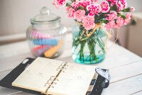Image of a scheduler and flowers on a desk