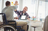 Man in a wheelchair high-fives another man