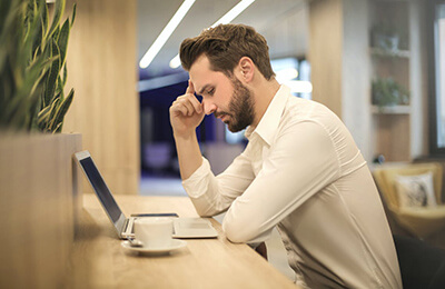 Man sitting at desk in front of laptop thinking