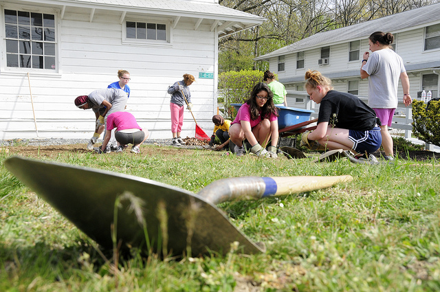 Shovel laying on grass in the foreground with young people helping with yardwork in the background