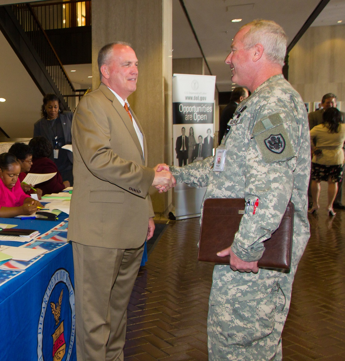 Soldier shaking hands with potential civilian employer in front of both at employment fair