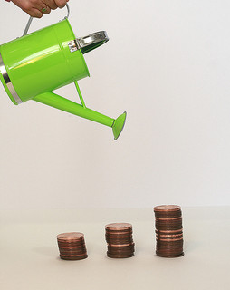 Image of watering can hovering over growing stacks of coins