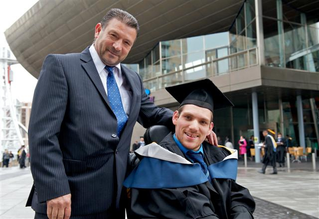 Man in suit standing proudly with young man in a wheelchair wearing a graduation cap and gown