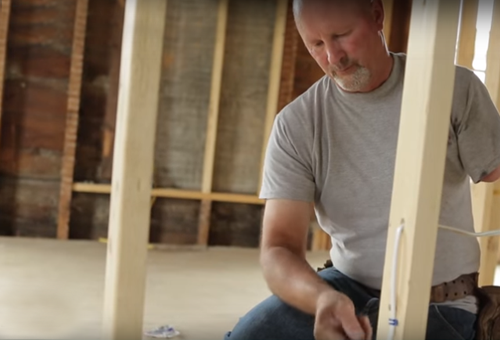 man working on house interior framing